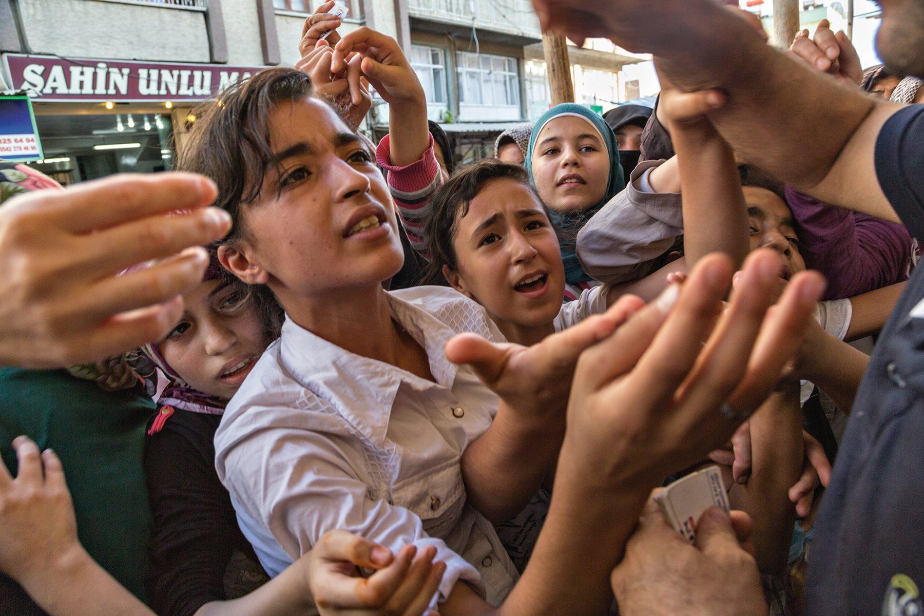 La vida no es fácil para los 350.000 sirios que se calcula se han establecido en la ciudad de Gaziantep y alrededores. Mujeres y niños se agolpan en torno a un panadero que reparte vales canjeables por pan (2015). John Stanmeyer/National Geographic