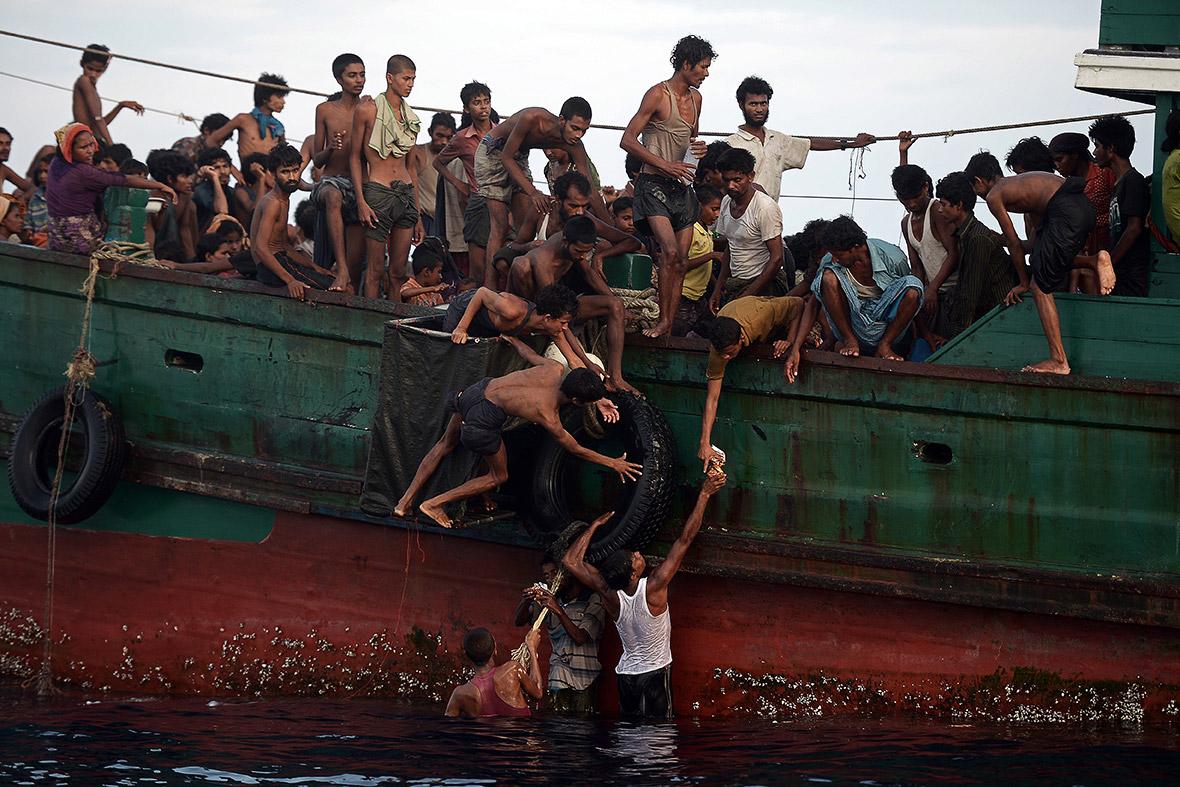 Tres hombres trasladan la comida lanzada desde el aire a otras personas que se han quedado en el barco (2015). Christophe Archambault/AFP