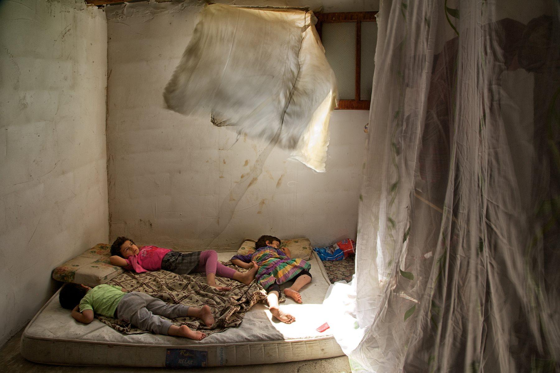 La búsqueda desesperada de una vivienda ha llevado a la familia de estos pequeños a instalarse en una granja. La habitación, que comparten seis personas, se alquila por 130 euros mensuales (2015). John Stanmeyer/National Geographic