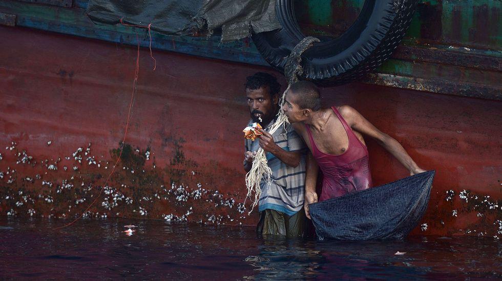 Hamid Husen (rohingya) y Muhammad Ehsan (bangladesi) comen alimentos lanzados por un helicóptero del ejército tailandés en un barco a la deriva en el mar de Andaman, Tailandia (2015). Christophe Archambault/AFP
