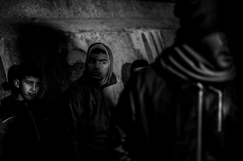 Jóvenes procedentes de Marruecos que esperan en una roca junto al puerto del enclave español de Melilla.  José Colón