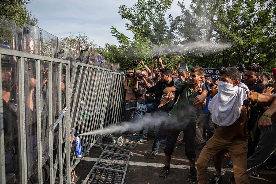 Policías húngaros lanzan gas pimienta a las personas que intentaban pasar la frontera desde Serbia después de pasar dos días bloqueados sin poder continuar su camino. Horgos, Serbia (2015). Olmo Calvo