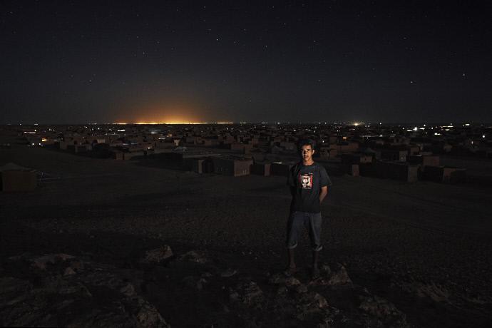 Azmah Laulad en el campamento de refugiados de Auserd, Argelia, con las luces de Tinduf en el fondo (2009). Andrew McConell/Médicos del Mundo