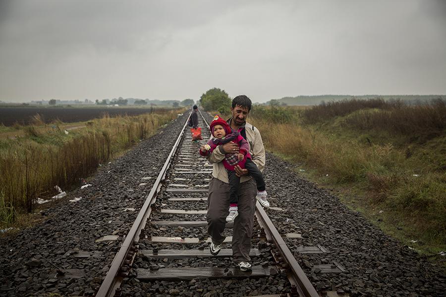 Un hombre camina por las vías del tren con su hijo pequeño después de cruzar la frontera entre Hungría y Serbia (2015). Olmo Calvo