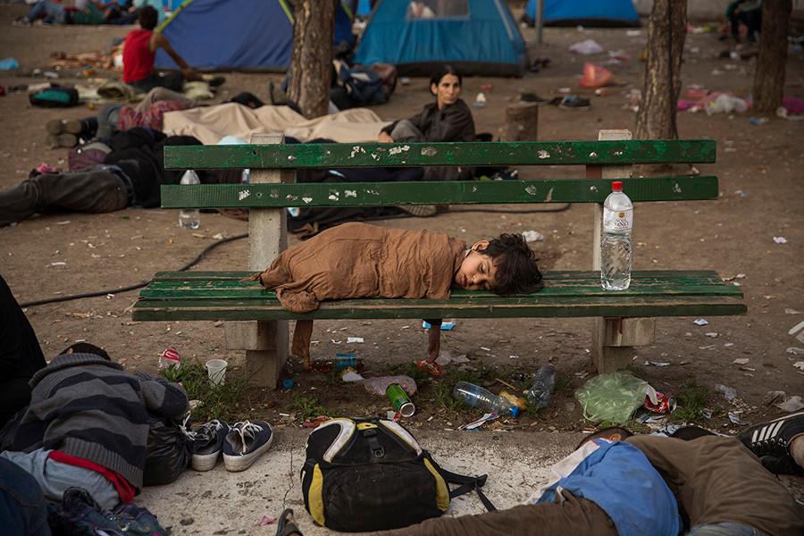 Un niño duerme en un banco del parque Bristol de Belgrado. Ese parque era donde pasaban la noche cientos de refugiados y refugiadas antes de continuar su camino hacia Hungría. Belgrado, Serbia (2015). Olmo Calvo