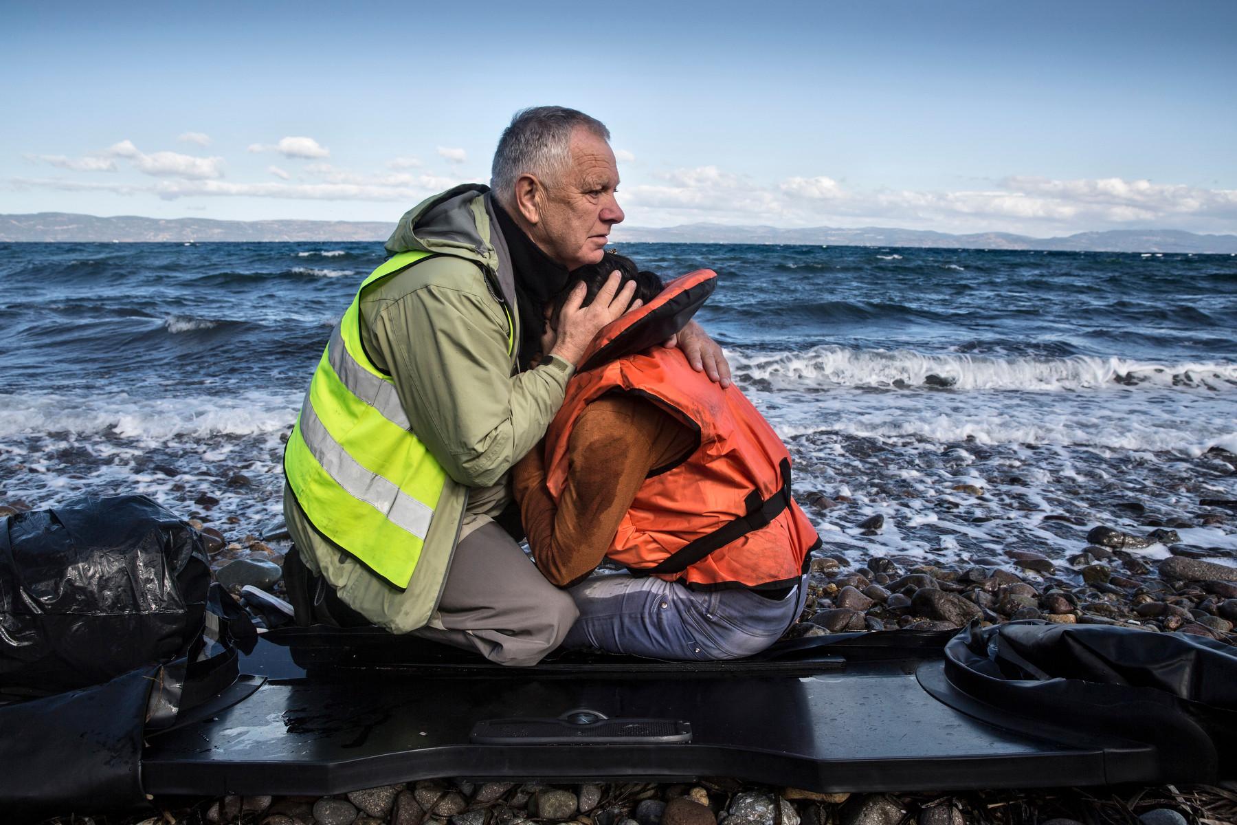 Voluntario consolando a una mujer refugiada recién llegada a Lesbos (2015). Paula Bronstein/Getty Images.