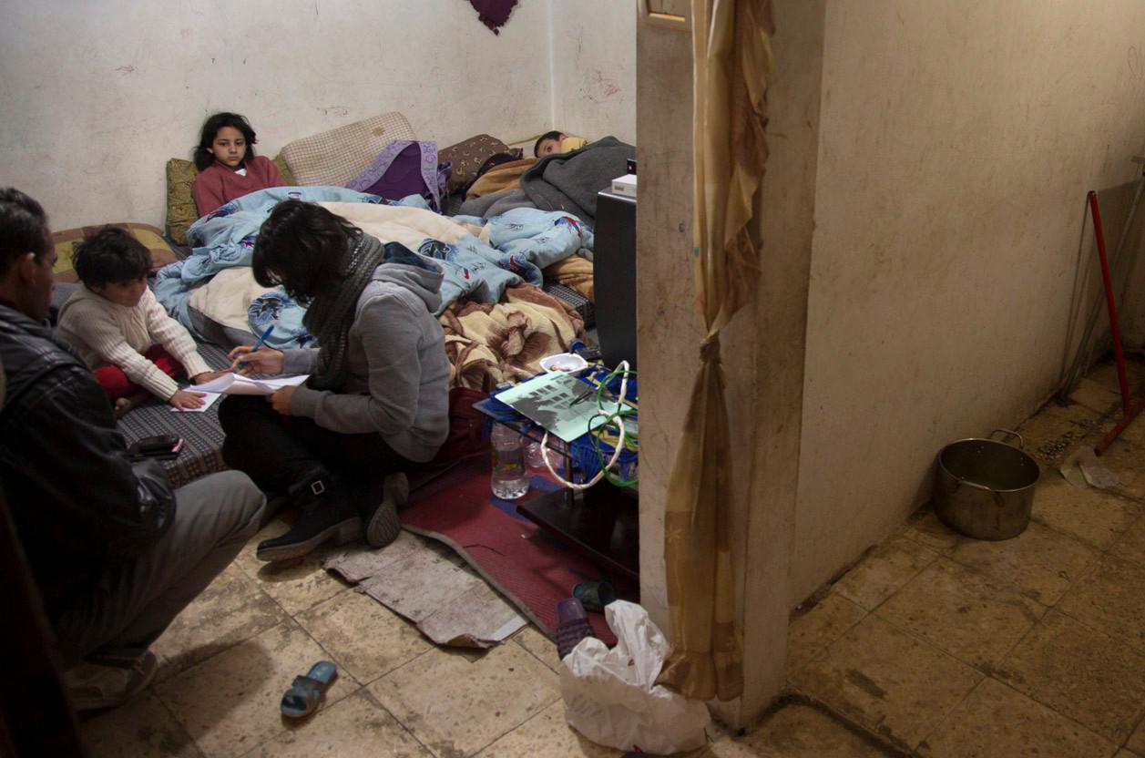Representante de ACNUR reunido con una familia de refugiados sirios que viven en un sótano en Jordania para evaluar sus necesidades (2014). Lucian Perkins