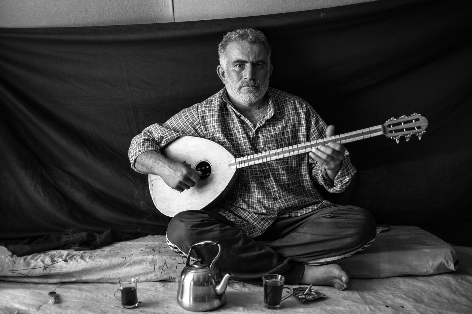 Abdulaziz en el campo de refugiados de Domiz (Kurdistán). Huyó de su hogar en Siria la noche que asesinaron a sus vecinos. La cosa más importante que pudo llevarse fue el instrumento que sostiene. Brian Sokol/ACNUR