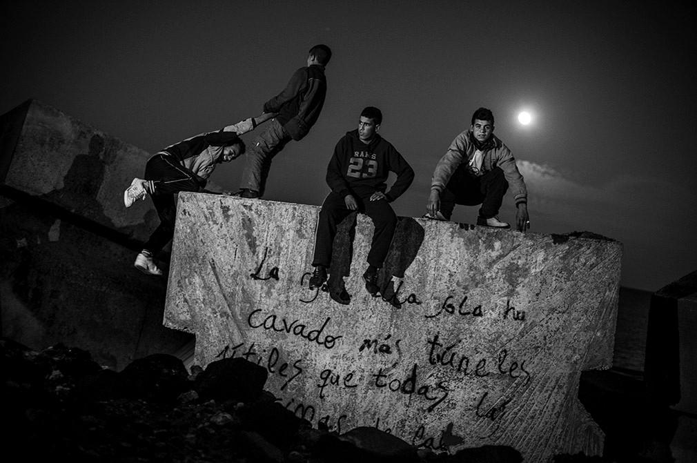 Niños marroquíes sentados en el dique junto al puerto de Melilla. José Colón