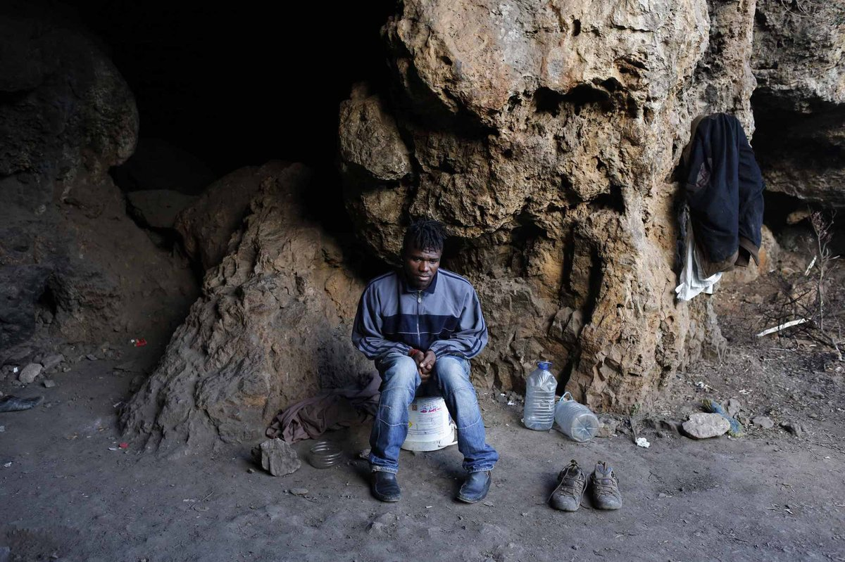 El camerunés Adria, sentado en su escondite junto a dos bidones de agua y un par de zapatos. Ceuta (2014). Juan Medina/Reuters