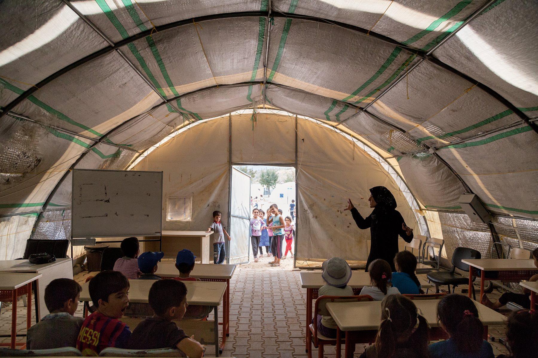 Los niños que viven en campamentos, como estos de Nizip 1, tienen más probabilidades de ser escolarizados que los que viven fuera de ellos (2015). John Stanmeyer/National Geographic