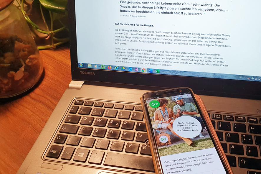 Das Foto zeigt ein Notebook mit daraufliegendem Smartphone, auf dem die (responsive) Webseite von Go. by Göing zu sehen ist