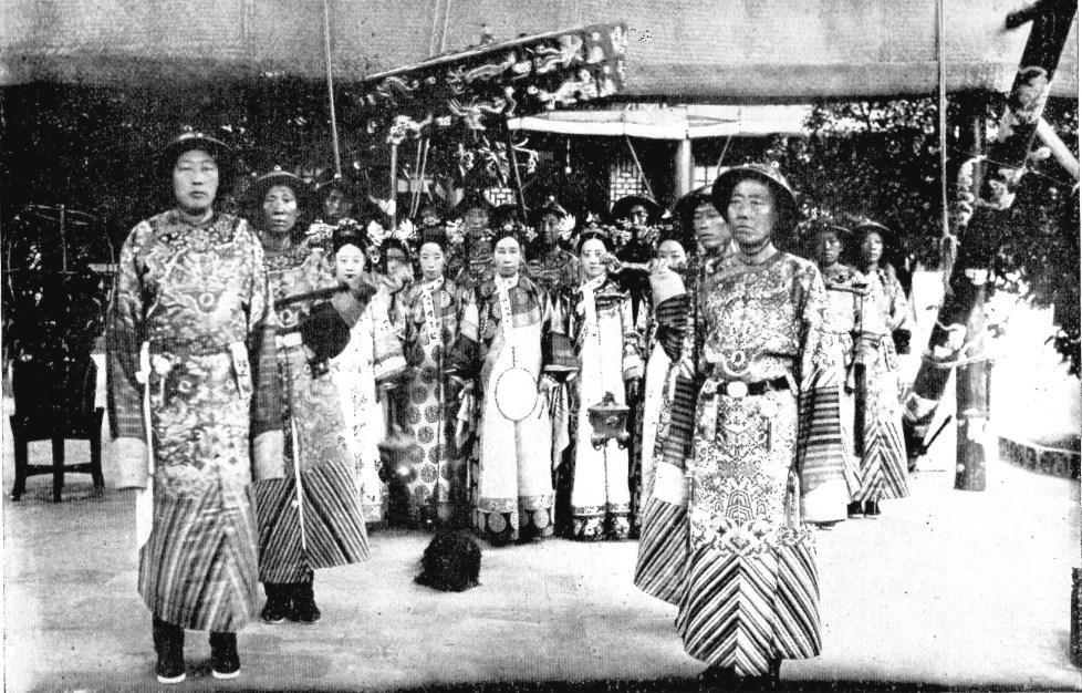 Sa Majesté Tseu-Hi avec l'impératrice consort (Loung-Yu) et la principale concubine (Jen Fei) de Sa Majesté Kouang-Siu, entourées de dames de la Cour et d'eunuques.