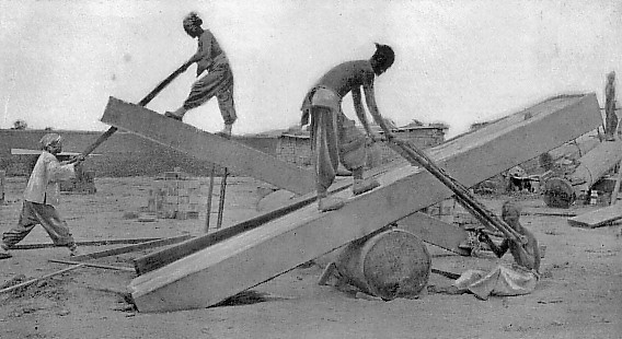 Charpentiers chinois sciant du bois de construction