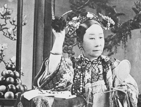 239. — S. M. l'Impératrice Tseu-hi se mirant dans la glace qu'elle tient de la main gauche.