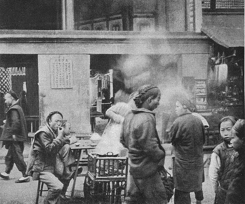 Dans une rue de Kouang-Tchan ; les habitants prennent fréquemment leur repas devant leur porte.