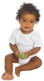 sitzendes Baby mit dunklen gekringelten Haaren und großen, dunklen Augen hält ein Spielzeug in seinen Händen. Es trägt einen weißen kurzärneligen Body.