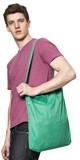 junger Mann mit einem altrosa T-shirt hat eine grüne Tasche lässig über die linke Schulter gehängt