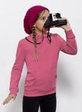 Mädchne trägt einen kecken pinken Pulloverund fotografiert mit einer Polaroidkamera etwas in der Ferne - vielleicht die tollen Produkte von Stanley&Stella