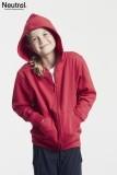 ein junges Mädchen kuschelt sich in ihre rote Kapuzenjacke, die Hände vergräbt sie in den Jackentaschen