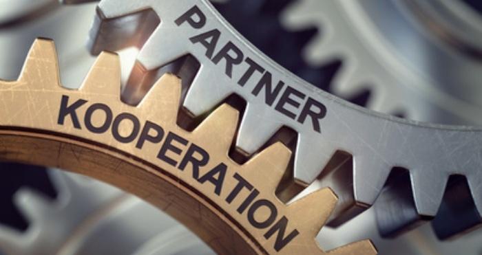 """Zwei Zahnräder """"Kooperation"""" und """"Partner"""" greifen ineinander"""