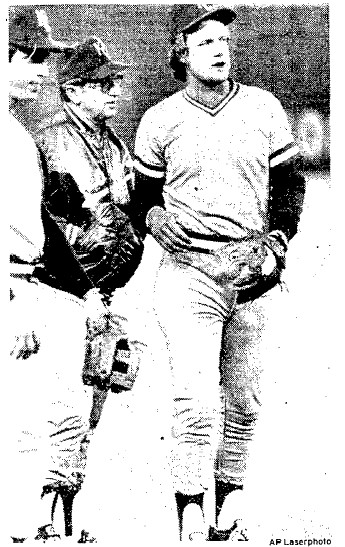 Royals manager Jim Frey checks out ailing slugger George Brett before the game.