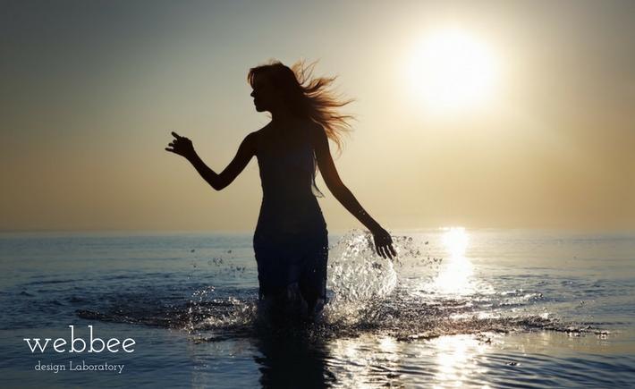 本年もどうぞよろしくお願いいたします!:逆光で海の浅瀬で水しぶきを上げて踊る女性