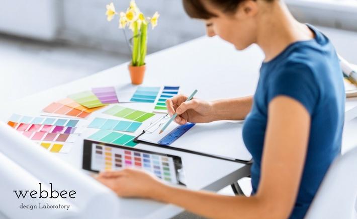 カラーサンプルを見ながらホームページのデザインを考える女性