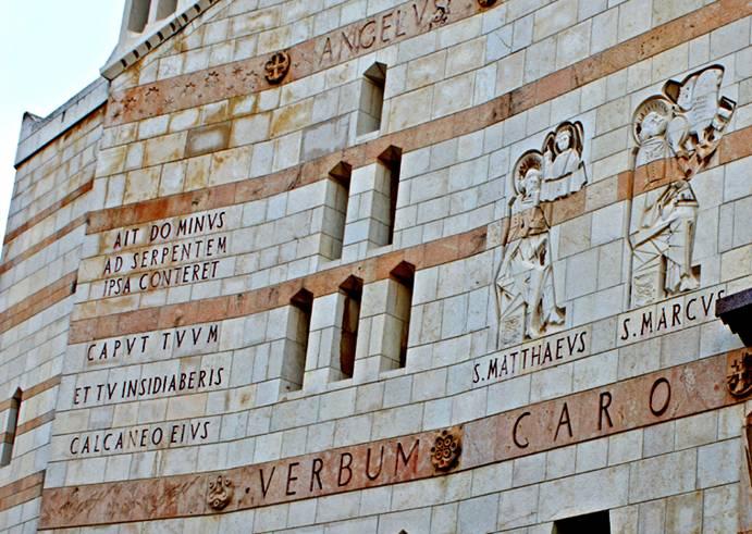 """Gros plan sur la partie gauche de la façade occidentale. On remarque la représentation des deux premiers évangélistes Matthieu et Marc, et la citation de la Génése: Dieu dit au serpent """"Elle t'écrasera la tête et toi tu la blesseras au talon"""" Gen 3 14-15"""
