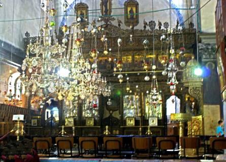 Derrière les lustres du sanctuaire, l'iconostase.