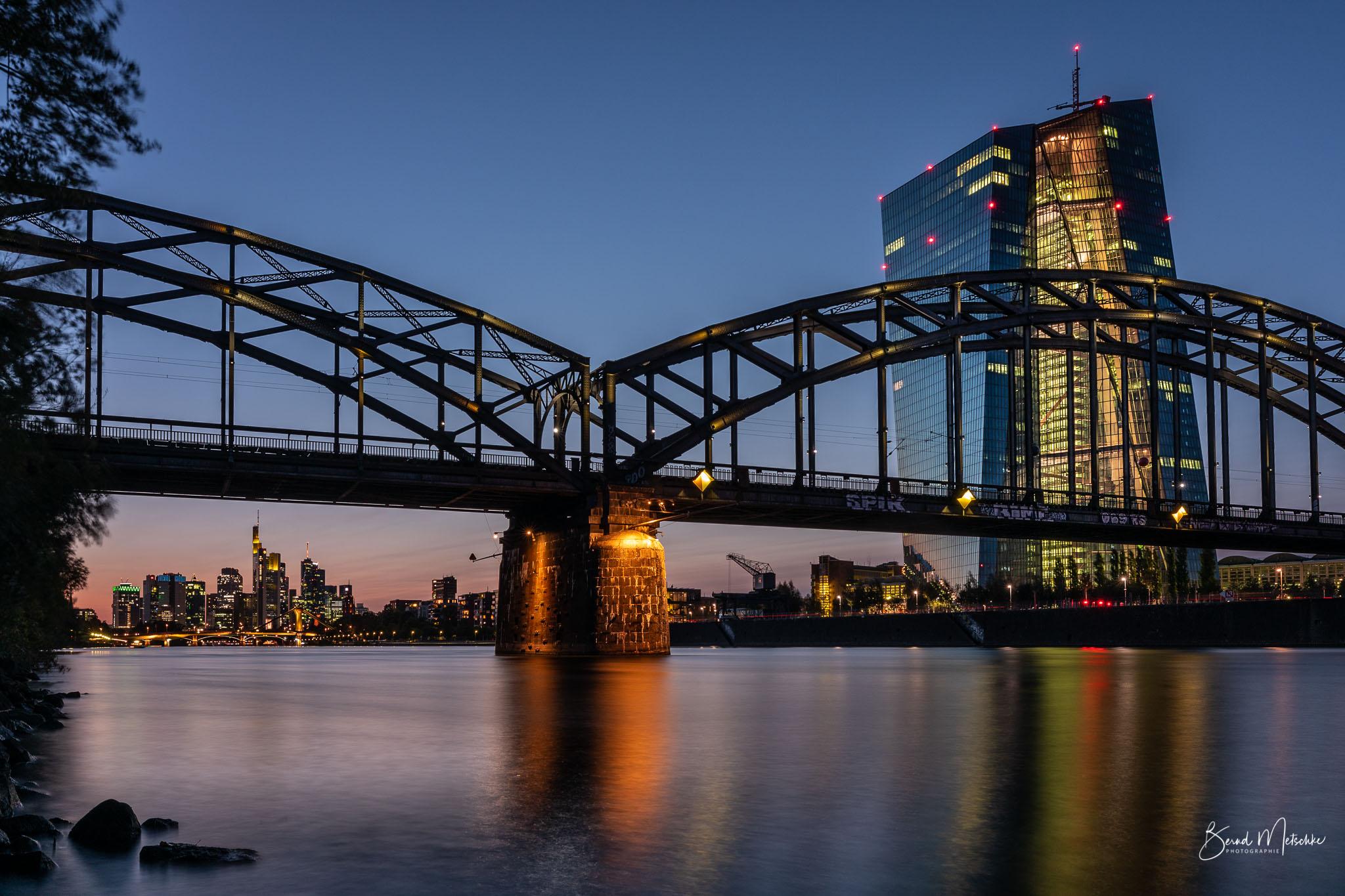 Die EZB vor der Frankfurter Skyline am Abend