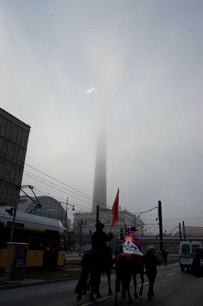 Als die Demo am Fernsehturm vorbeizieht, bricht die Sonne durch die dichten Wolken. | When the demo passes the TV tower, sun breaks through the thick clouds.