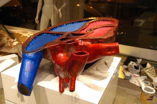 Corazón Decorativo en espuma y silicona, iluminado con leds, sirve de expositor para pequeños productos en las superficies rojas y azules de terciopelo.