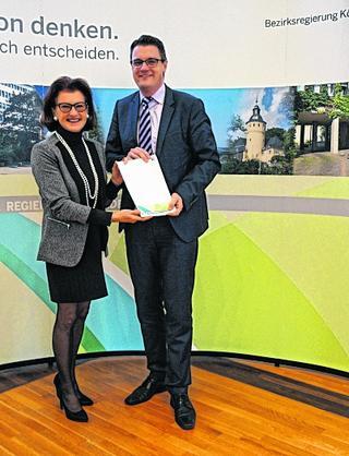Bürgermeister Tim Grüttemeier erhält den Bewilligungsbescheid von Regierungspräsidentin Gisela Walsken.