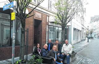 """CDU-Vertreter vor den beiden Häusern, die abgerissen werden, vorne rechts Siegfried Pietz, hinten Mitte Martin Hennig. Hier soll dereinst der """"Quartiersplatz"""" entstehen. Foto: Wolfgang Wynands"""
