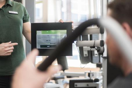Eine Trainerin zeigt einem Kunden das Gerätetraining