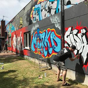 Eine in der Perspektive sich nach Hinter verjüngenden Wand mit mehreren angefangenen Graffitis und ganz vorne der Graffiti Sprüher Cask. Daneben ein Bild von Mirko Machine und im Hintergrund steht Samy Deluxe auf einer Leiter.