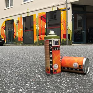 Auf einer Fassade steht in großen gelb und orangen Buchstaben der Name Ohm, die Buchstaben überlagern ein grünes Graffiti. Im Vordergrund steht ein schwarzes Auto.