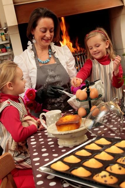 Victoire et Eglantine préparent sous l'oeil de Virginie un gâteau moelleux à l' orange