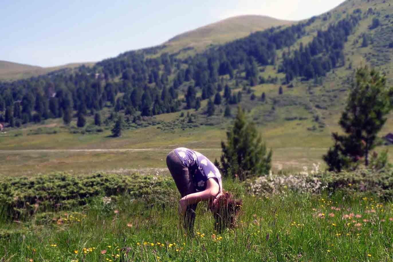 AUSATEM: Stehende Vorwärtsbeuge. Der Atem zieht den Bauch sanft ein und rundet die Wirbelsäule. Schau mal, was da so im Gras rumwuselt.