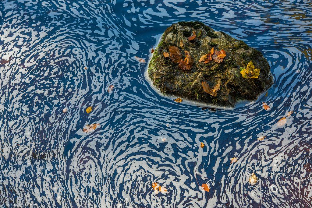 """An den Rändern des Flusses bilden sich ab und zu Schaum-Strukturen, die um die umgebenden Steine """"kreisen"""" (B199)"""