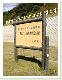 写真中の文字パネル部分が木目仕上 柱、横木部分が樹皮(桜)仕上