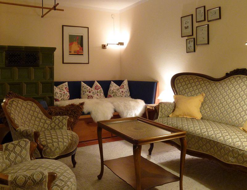 Wohnzimmer mit Kachelofen und großzügiger Ofenbank