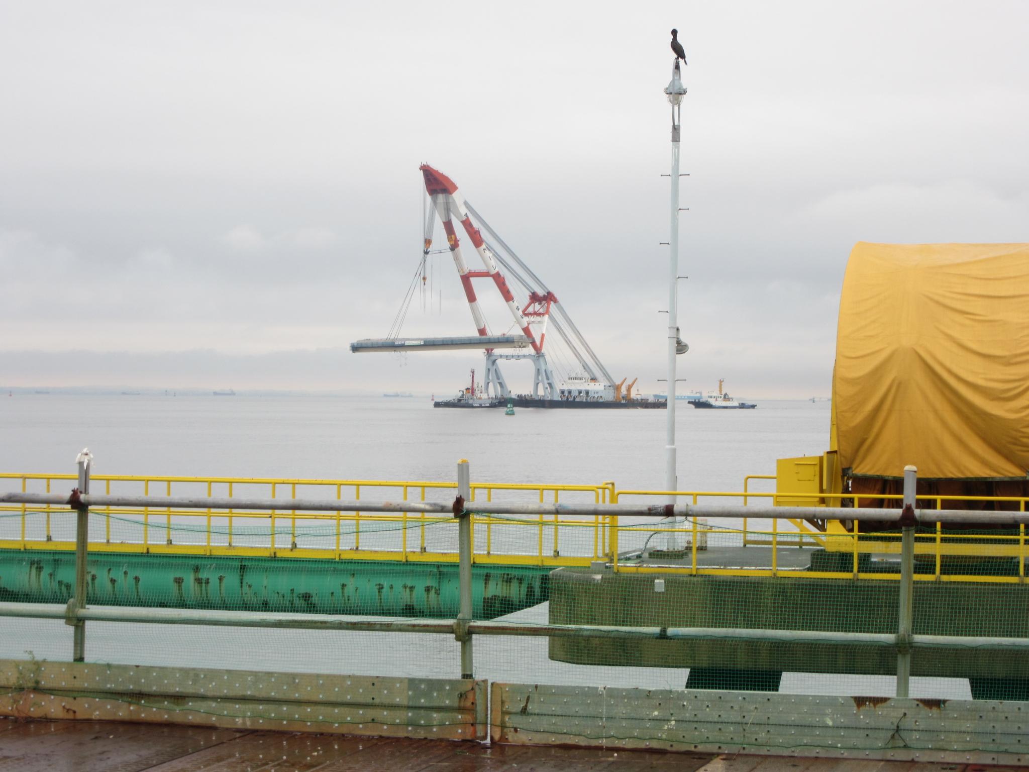 橋桁を起重機船で吊り上げて、沖合いから運ぶ様子