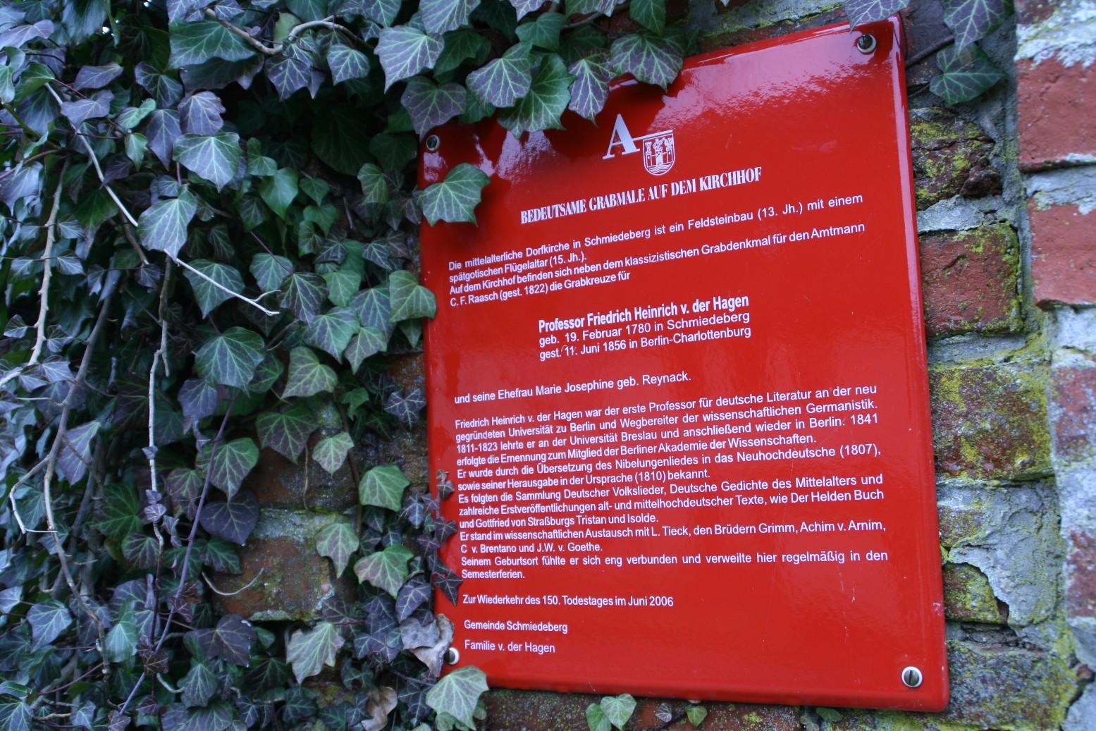 Eine Tafel an der Friedhofsmauer weist auf die Gräber Friedrich Heinrichs von der Hagen und seiner Frau hin.