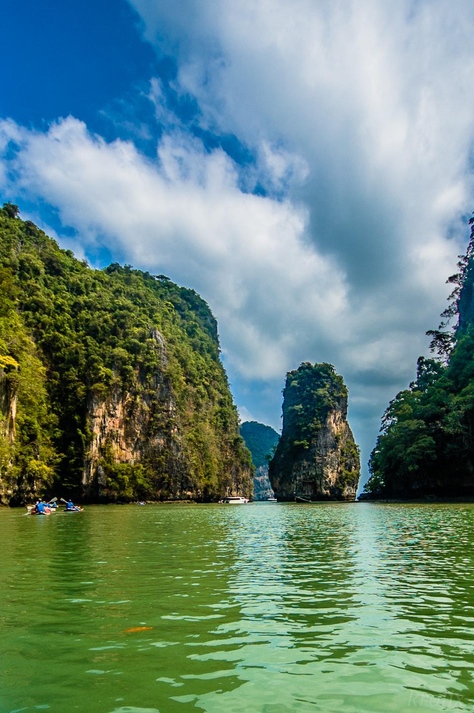 Вода очень зелёная, кругом странные высоченные острова-скалы...