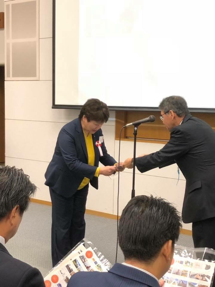 審査委員長から受賞の盾が手渡されました。