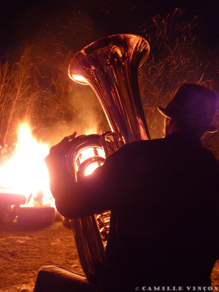 Musicien au bord d'un feu célébrant la fin de l'hiver.