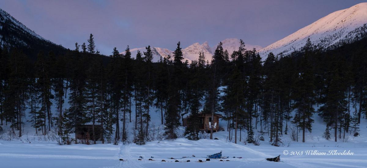 En arrière-plan, une cabane en rondins abandonnée par des américains, qui fut notre refuge pour la nuit. Au premier plan, les chiens et le traîneau.
