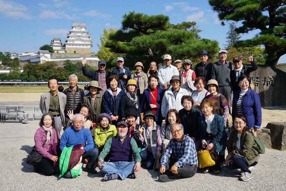 遠景の姫路城をバックに記念写真。